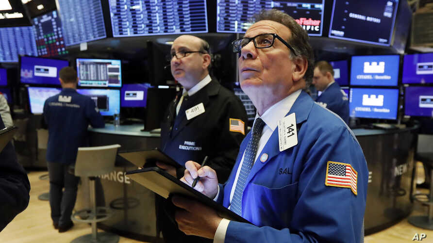 Traders Andrew Silverman, left, and Sal Suarino work on the floor of the New York Stock Exchange, Tuesday, Feb. 25, 2020…