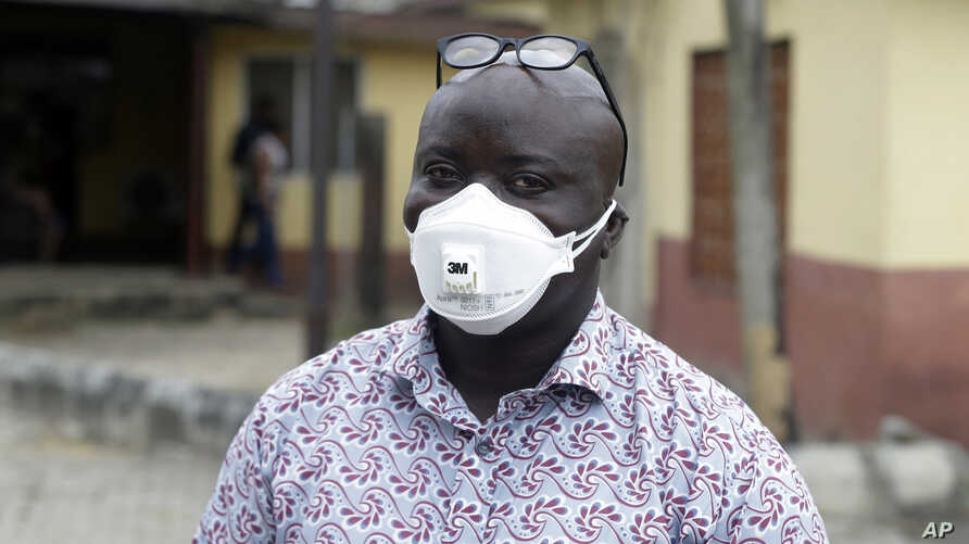 A man wearing a face mask walks outside Yaba Mainland hospital where an Italian citizen - the country's first case of the COVID.