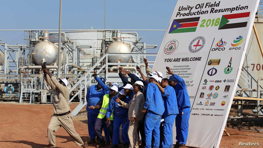 Workers take a photo during a ceremony marking the restarting of crude oil pumping at the Unity oil fields in South Sudan,…