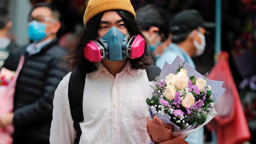A man wears a gas mask as he holds a bouquet of flowers, following the outbreak of the novel coronavirus on Valentine's Day in Hong Kong, China, Feb. 14, 2020.