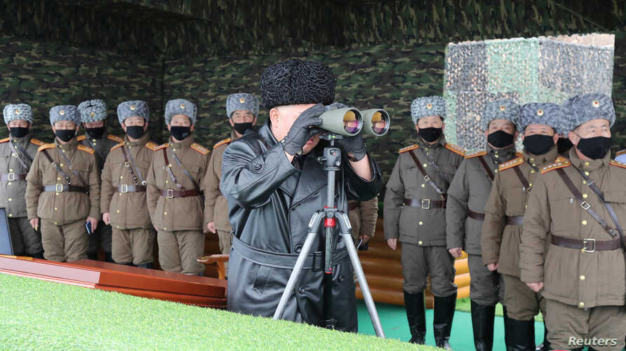 North Korean leader Kim Jong Un uses binoculars while attending a drill by a unit of the Korean People's Army (KPA), North…