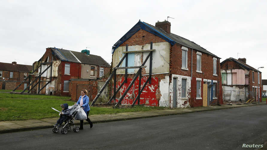 A woman pushes a pram along a semi-derelict terraced street in the Gresham area of Middlesbrough, northern Britain, Jan. 20, 2016. Asylum seekers in the northern English town of Middlesbrough are suffering abuse.