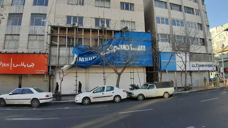 A Samsung Electronics advertising banner is taken down from a home appliance storefront in Tehran, in this image published Feb. 13, 2020 by Iran's state-approved Hamshahri newspaper.