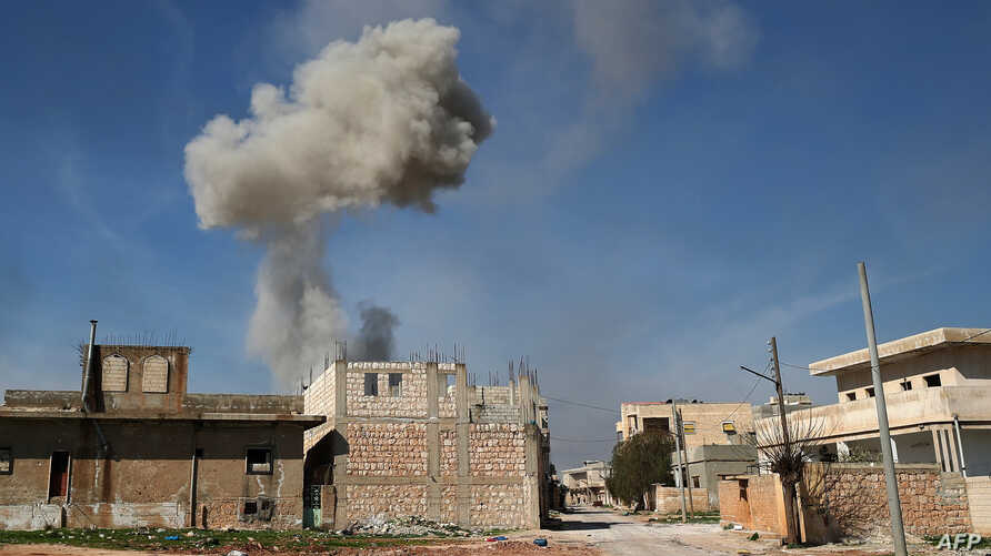 Smoke billows over the town of Saraqib in the eastern part of the Idlib province in northwestern Syria, following bombardment by Syrian government forces, Feb. 27, 2020.