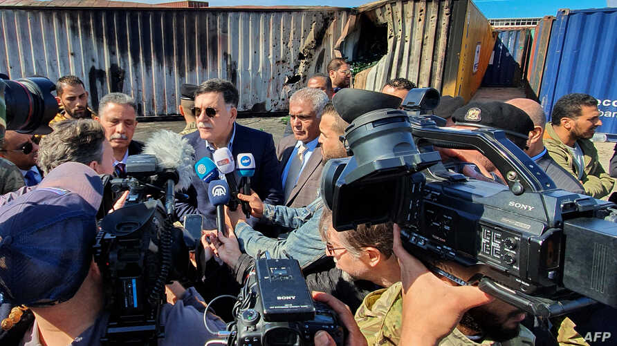 Prime Minister of Libya's U.N.-recognized Government of National Accord (GNA) Fayez al-Sarraj, flanked by journalists, visits the port in the capital Tripoli after it was hit by rocket fire, Feb. 19, 2020.
