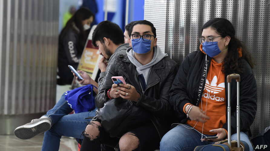 Passengers wearing protective masks are seen at the International Airport in Mexico City, Mexico, Feb. 28, 2020.