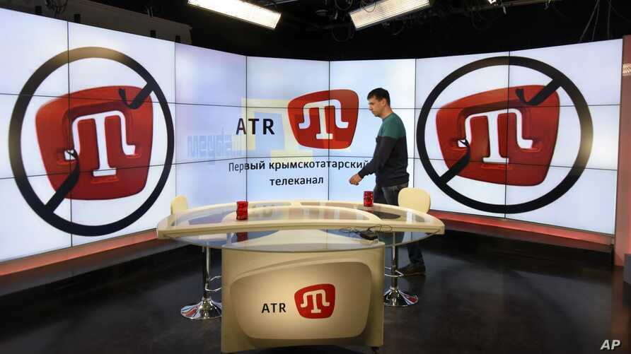 FILE - An employee of Crimean Tatar ATR TV walks in a studio in Simferopol, Crimea, March 31, 2015. Following Crimea's annexation by Russia in March of 2014, ATR lost its license and resumed broadcasting from Ukraine's capital, Kyiv, in June of 2015.
