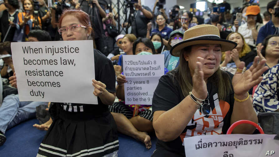 Supporters of Thailand's Future Forward Party display placards denouncing a decision by the country's Constitutional Court to dissolve the party, in Bangkok, Thailand, Feb. 21, 2020.