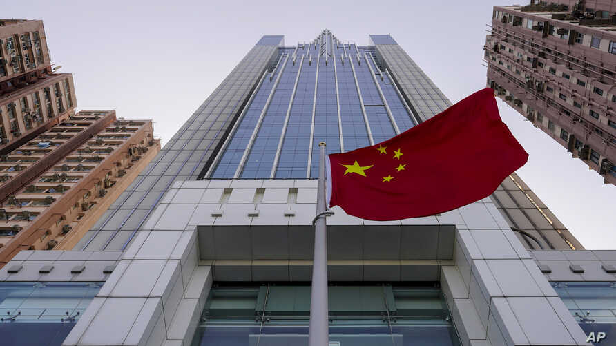 FILE - A Chinese national flag flutters outside China's liaison office building in Hong Kong, Jan. 6, 2020.