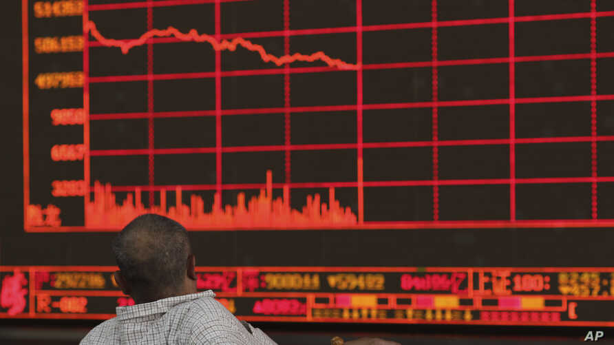 FILE - An investor watches as the Shanghai Composite Index falls at a brokerage in Beijing, China, May 6, 2019.