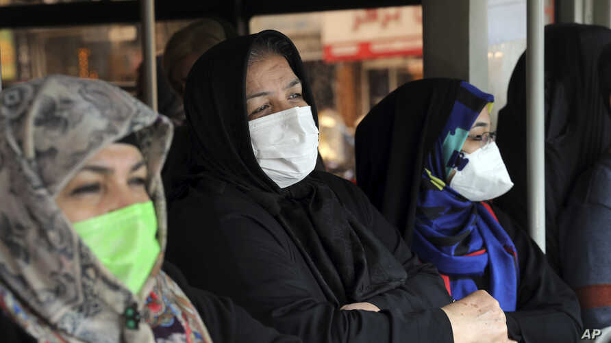 Commuters wear masks on a public bus in downtown Tehran, Iran, Feb. 23, 2020.