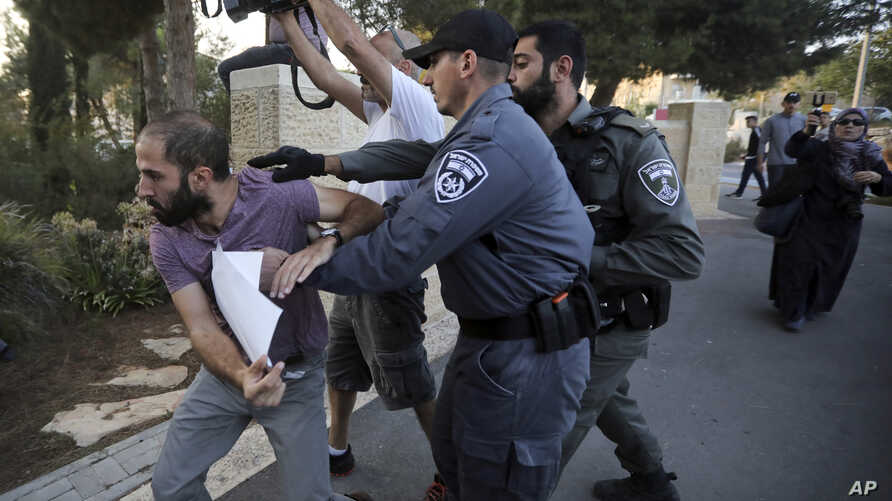 FILE - Israeli police try to restrain a man during a protest outside a hospital where Samir Arbeed, a Palestinian suspect in a deadly West Bank bombing, is being treated, in Jerusalem, Oct. 1, 2019.