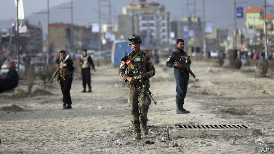 Afghan security personnel are seen at the site of bomb explosion in Kabul, Afghanistan, Feb. 26, 2020.