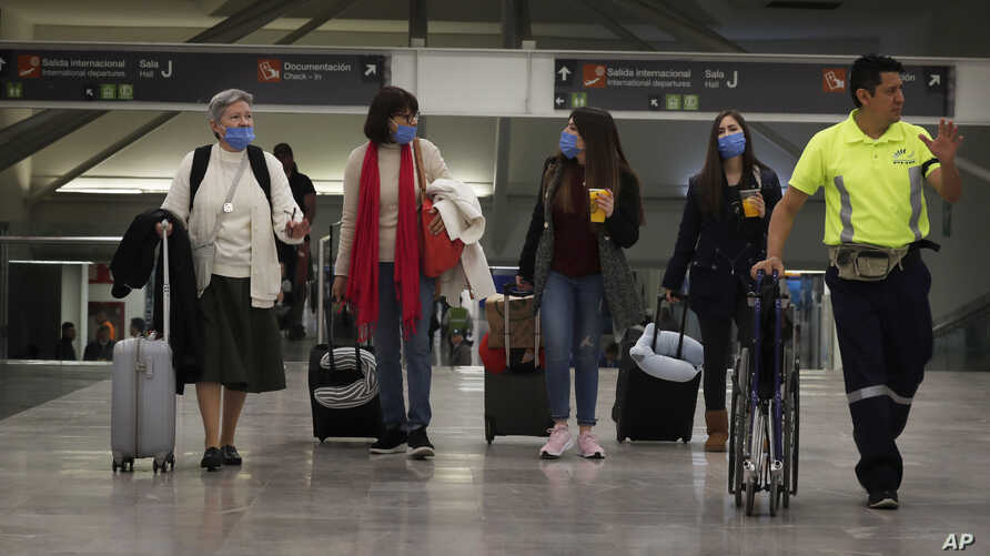 Travelers wear protective masks as a precaution against the coronavirus, at the airport in Mexico City, Mexico, Feb. 28, 2020.
