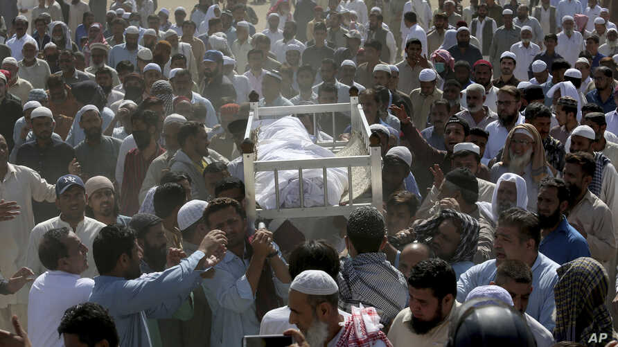 People carry the body of a victim of a toxic gas leak, during funeral prayers for the deceased, in Karachi, Pakistan, Feb. 17, 2020.