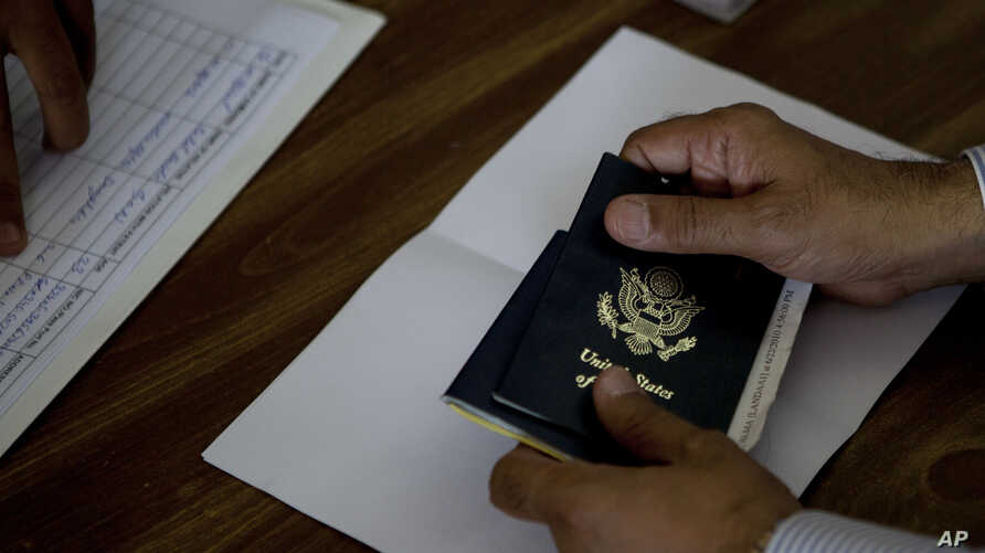FILE - A person holds a U.S. passport at a reporting center in Islamabad, Pakistan, July 29, 2010.
