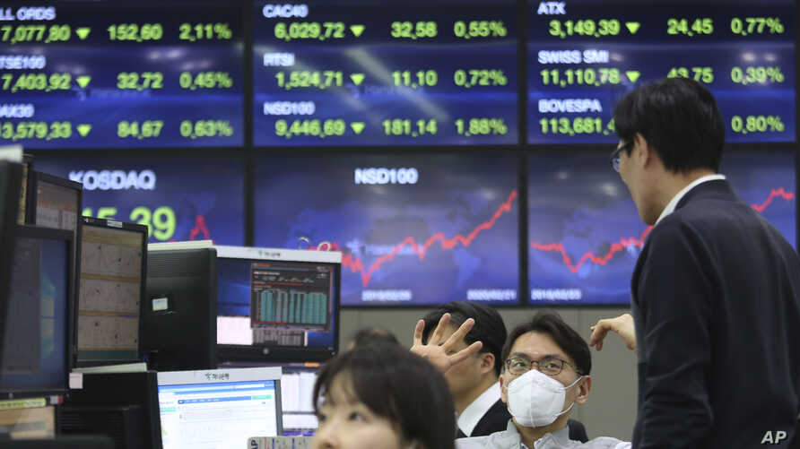 A currency trader wears a face mask at the foreign exchange dealing room of the KEB Hana Bank headquarters in Seoul, South Korea, Feb. 24, 2020.
