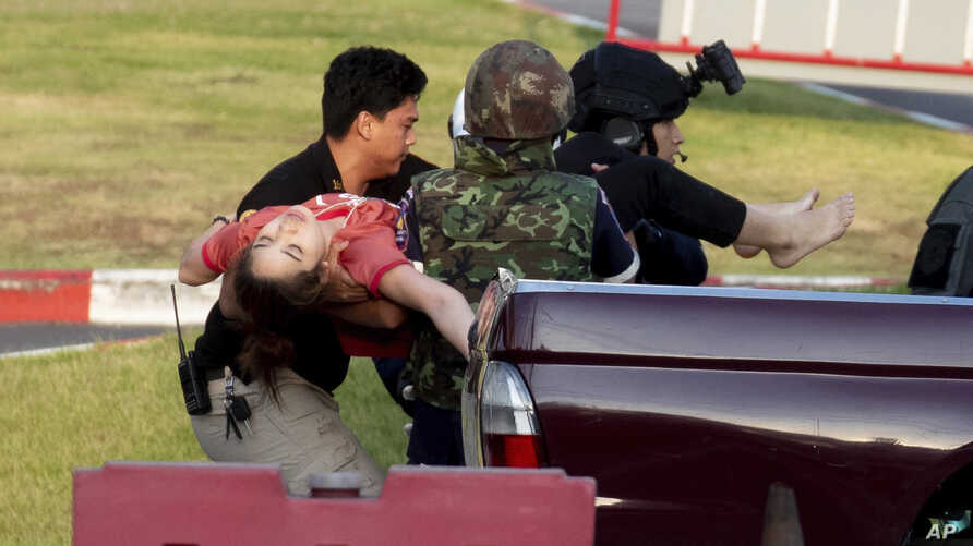 Armed commando soldiers carry a woman who fainted, out of Terminal 21 Korat mall where a mass shooting took place in Nakhon Ratchasima, Thailand.