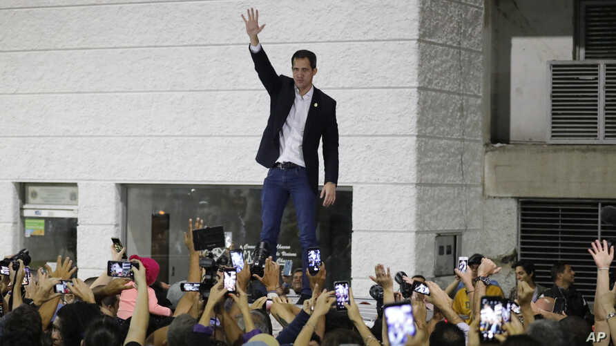 Opposition leader Juan Guaido waves to supporters during a rally at Bolivar Plaza in Chacao, Venezuela, Feb. 11, 2020.