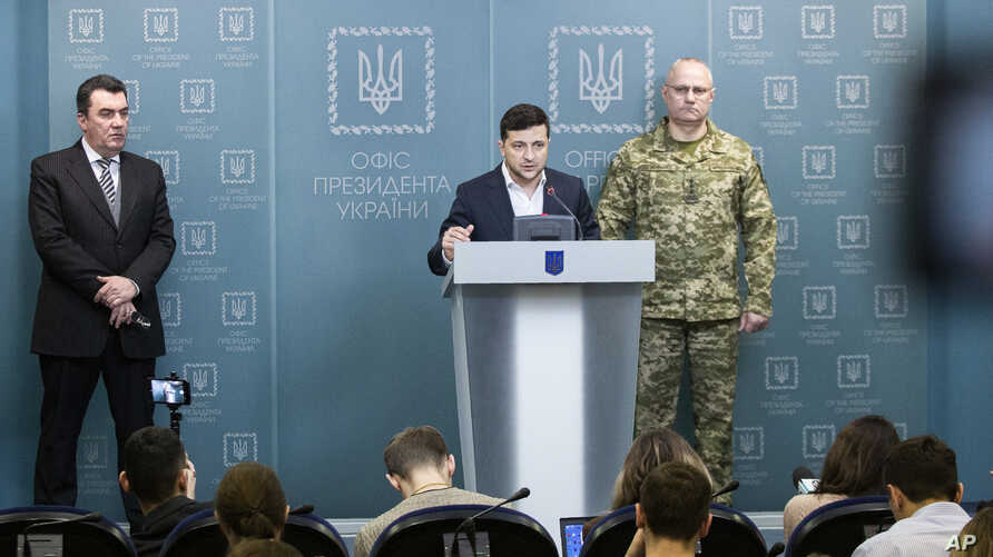 In this handout photo provided by the Ukrainian Presidential Press Office, Ukrainian President Volodymyr Zelenskiy speaks to the media at a briefing following a Security Council meeting in Kyiv, Ukraine, Feb. 18, 2020.