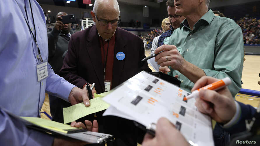 A precinct secretary and other officials look over documents at a caucus in Des Moines, Iowa, Feb. 3, 2020.