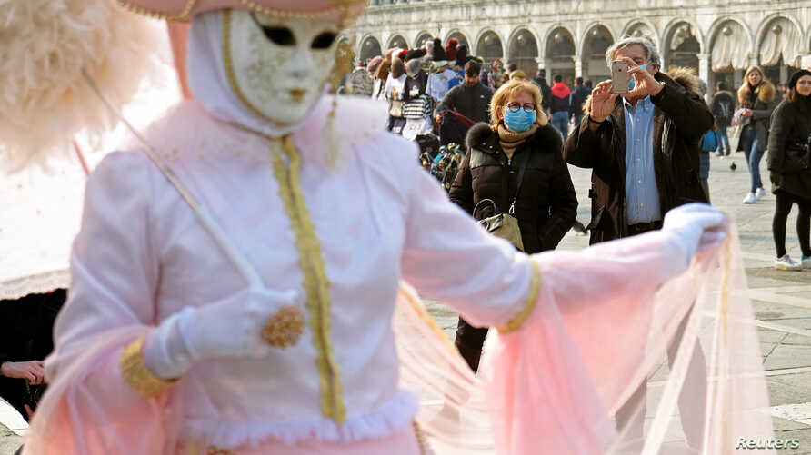 People wear protective face masks in St. Mark's Square after the last days of Venice's Carnival were cancelled due to the coronavirus, in Venice, Italy, 24, 2020.
