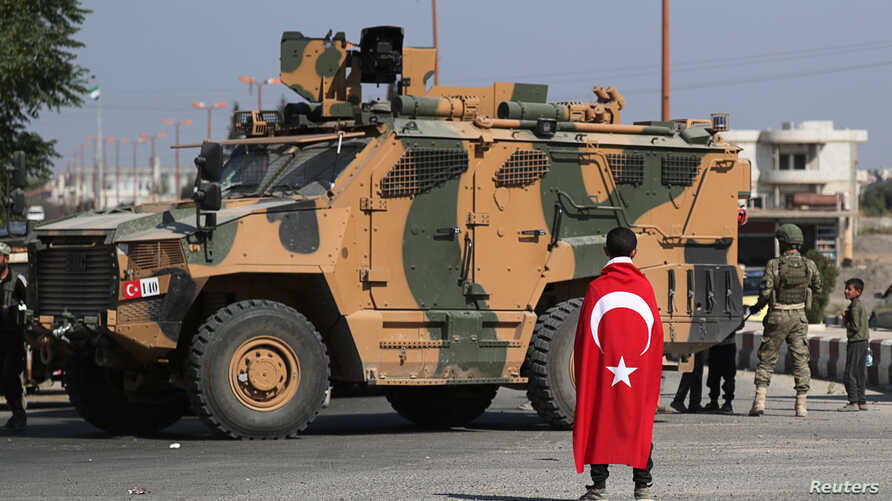 FILE - A boy, with a Turkish flag draped over his shoulders, stands in front of a Turkish military vehicle in the town of Tal Abyad, Syria, Oct. 23, 2019.
