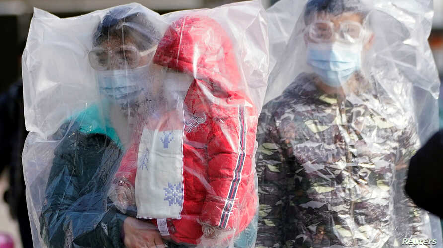 Passengers wearing masks and covered with plastic bags walk outside the Shanghai railway station in Shanghai, China, as the country is hit by an outbreak of the coronavirus, Feb. 9, 2020.
