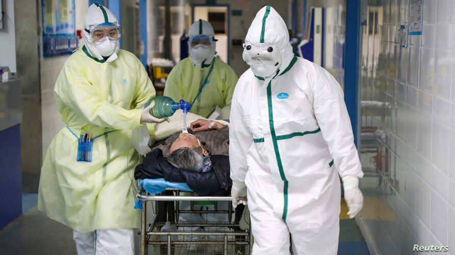 FILE - Medical workers in protective suits move a patient at an isolated ward of a hospital in Wuhan, China, Feb. 6, 2020.
