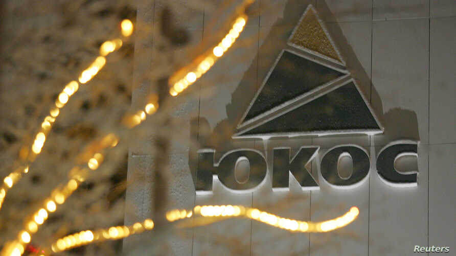 FILE - The Yukos logo is seen in its Cyrillic rendering on the wall of the headquarters building of the now defunct oil giant in the Russia's northern city of Nefteyugansk, Dec. 19, 2004.