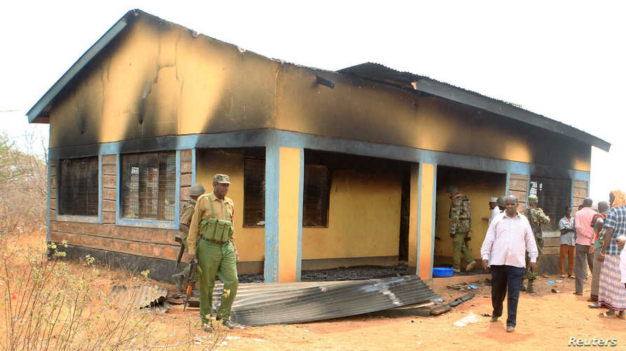 Security officers and residentAFILE - Security officers and residents assess the damage at Arabia Boys Secondary School after suspected al-Shabaab militants threw an explosive device at a teacher's house in Mandera county, Kenya, Oct. 10, 2018.  assess the damage at Arabia Boys Secondary School after suspected al Shabaab militants threw an…