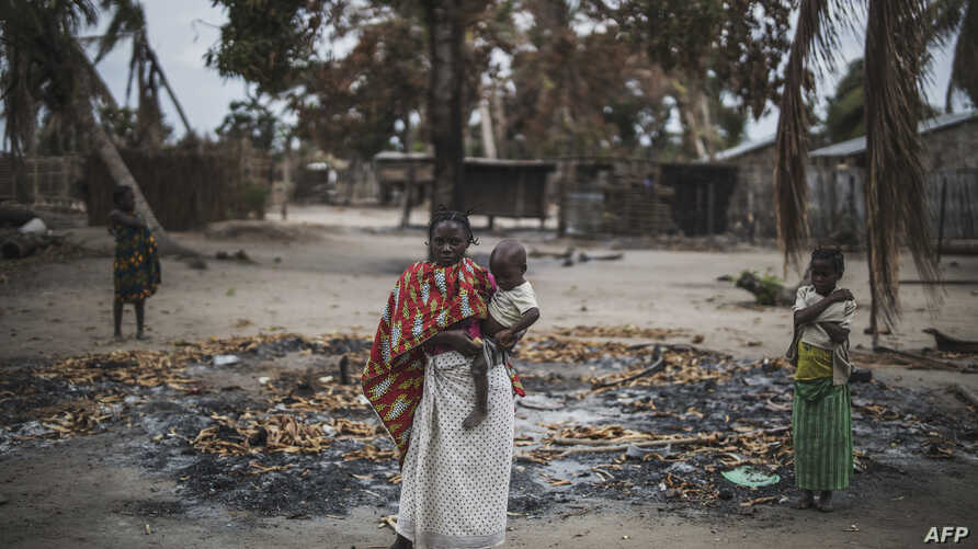 A woman holds her younger child while standing in a burned out area in the recently attacked village of Aldeia da Paz outside…