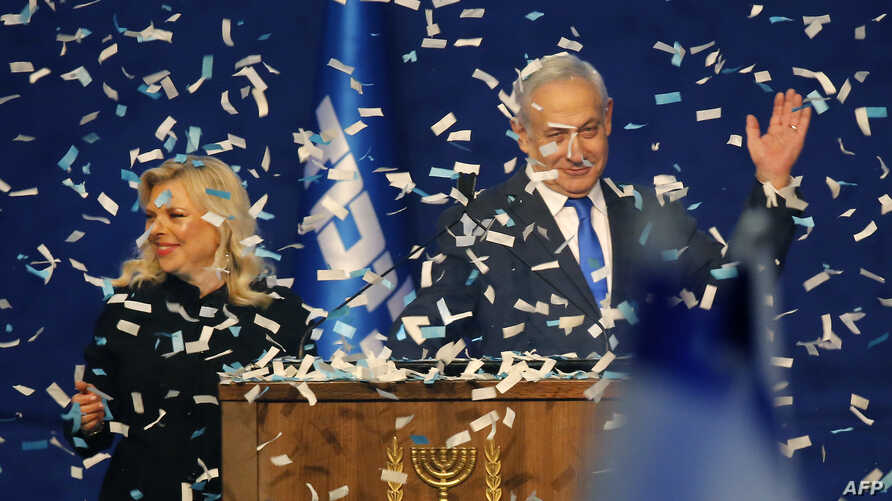 Israeli Prime Minister Benjamin Netanyahu and his wife Sara address supporters as confetti falls upon them at the Likud party…
