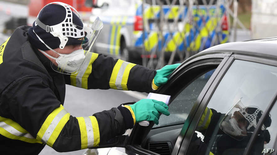 A Czech special police officer, with a protective mask, checks the temperature of a driver during sanitary checks at the border…
