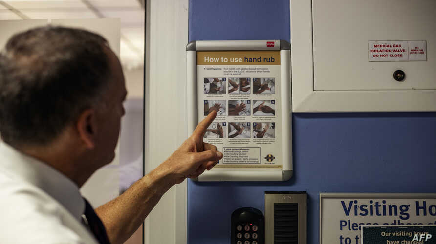 Doctor and Netcare Group Chief Executive Officer (CEO) Richard Friedland (R) explains how to wash hands at the Netcare…