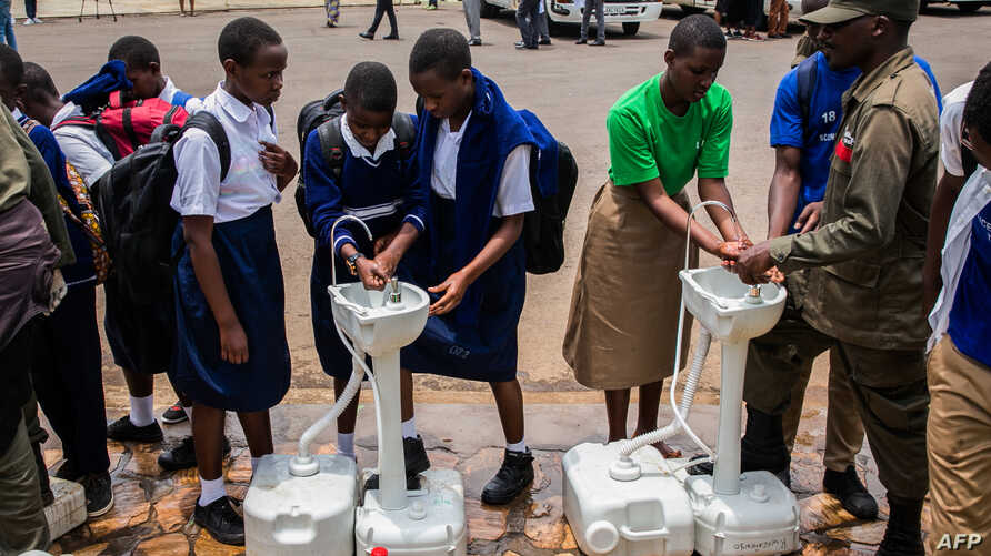 Secondary school students wash their hands at temporary hand washing point before they return home as Rwandan Government…