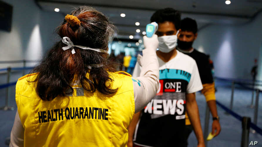 Health Quarantine officer checks people with a thermal scanner after Indonesia confirmed its first cases of coronavirus disease.