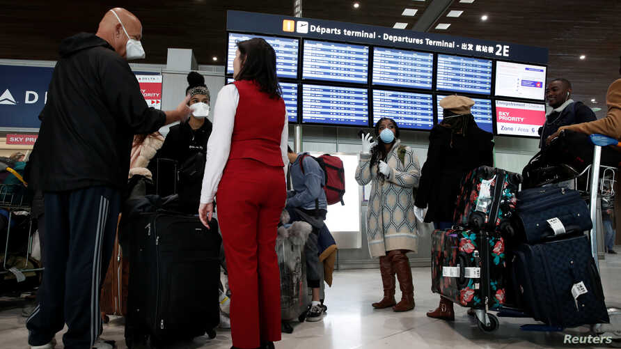 Travellers wearing protective masks stand at Delta Air Lines ticketing desk at Paris Charles de Gaulle airport.