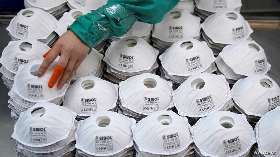 FILE - Masks are seen on a production line manufacturing masks at a factory in Shanghai, China January 31, 2020.