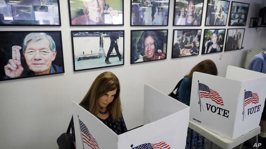 FILE - Voters fill out their ballots at the Los Angeles County Registrar of Voters office in Norwalk, Calif.