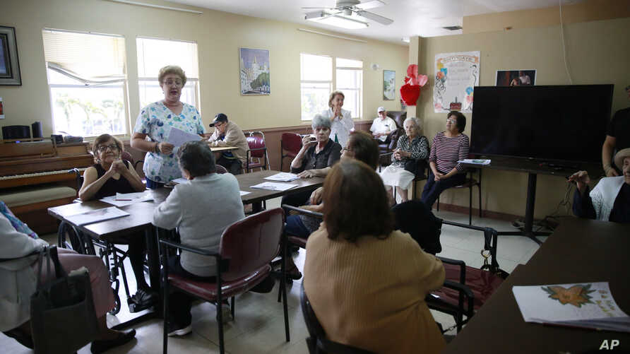 Alina Canel, nursing assistant, talks with the at the COVD-19 virus and how to care for themselves by washing their hands at Little Havana Activities and Nutrition Centers of Dade County, Inc., in Miami, March 4, 2020.