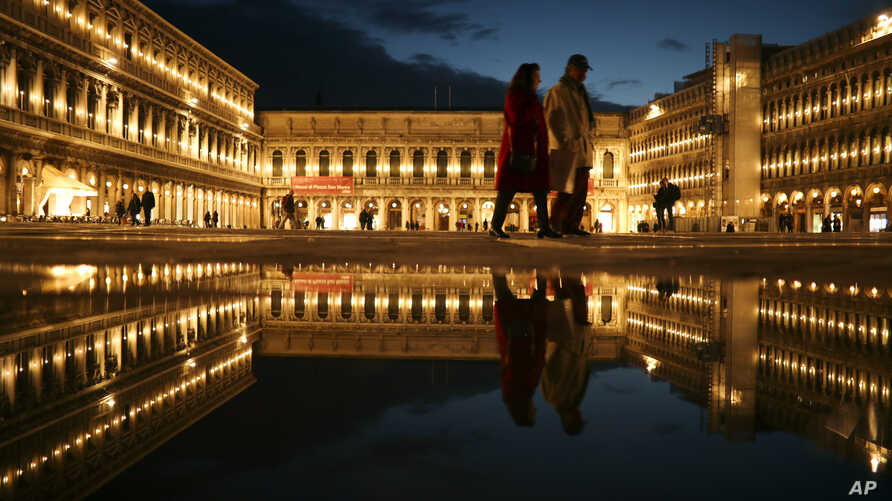 Locals and tourists walk along a nearly empty St. Mark's square in Venice, Italy, Tuesday, March 3, 2020.