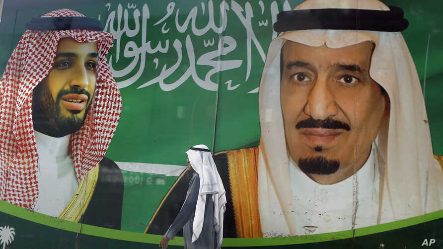 A man walks past a banner showing Saudi King Salman, right, and his Crown Prince Mohammed bin Salman, outside a mall in Jiddah, Saudi Arabia, March 7, 2020.