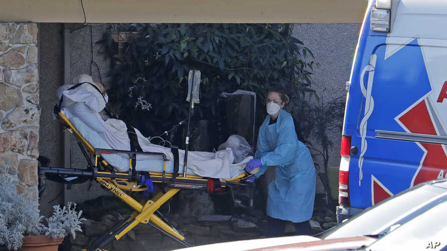 A patient is loaded into an ambulance at the Life Care Center in Kirkland, Wash. March 9, 2020, near Seattle.