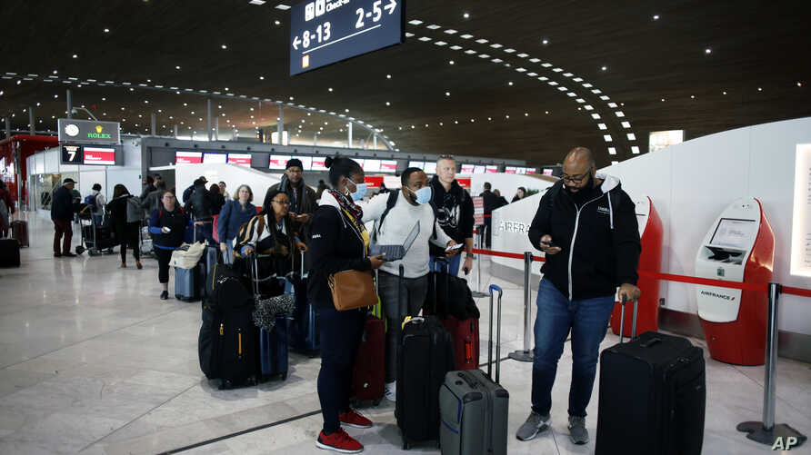 Passengers wait in front of the desk of Air France at the Roissy Charles de Gaulle airport, north of Paris, Thursday, March 12, 2020.