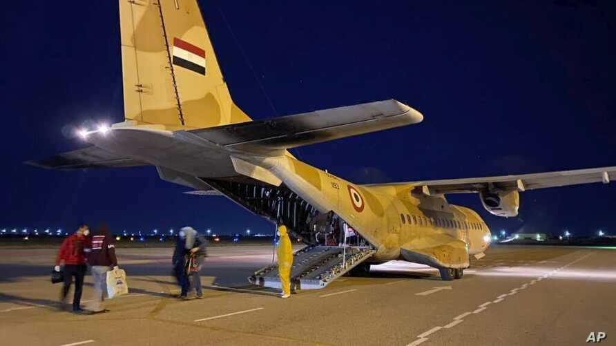 FILE - An Egyptian military plane waiting to take tourists who tested positive for the new coronavirus from Luxor to quarantine facilities on Egypt's north coast, March 8, 2020.