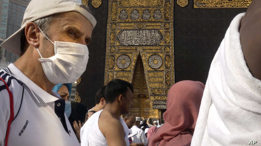 A relatively few number of Muslims pray around the Kaaba, the cubic building at the Grand Mosque, in the Muslim holy city of Mecca, Saudi Arabia, Thursday, March 5, 2020.