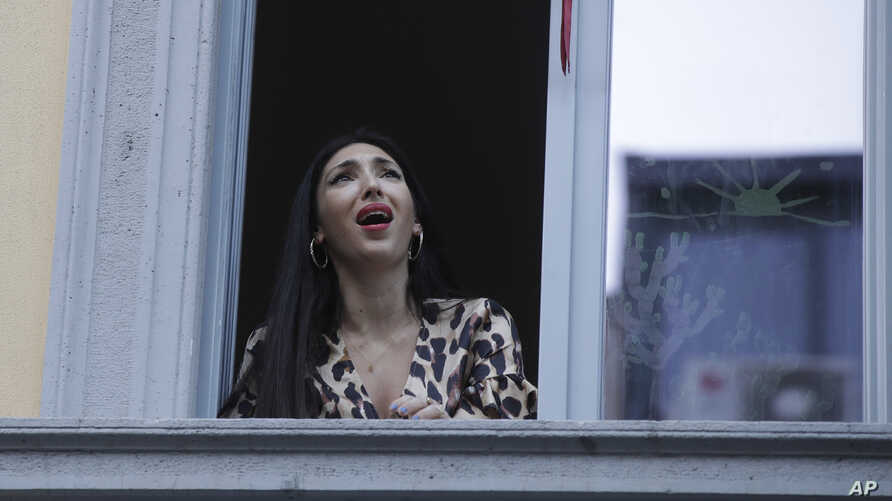 Opera singer Laura Baldassari leans out of her window to sing during a flash mob launched throughout Italy to bring people…