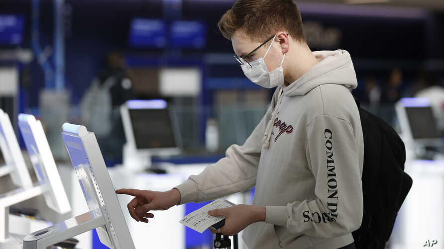 New York University student Hector Medrano, of Los Angeles, checks in for his flight using a touchscreen Saturday, March 14, 2020, at jetBlue's terminal in John F. Kennedy International Airport in New York.
