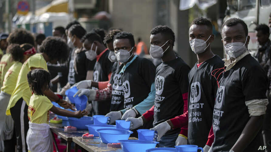 Volunteers stand ready to provide soap and water for participants to wash their hands against the new coronavirus at a women's 5km fun run in the capital Addis Ababa, Ethiopia, March 15, 2020.